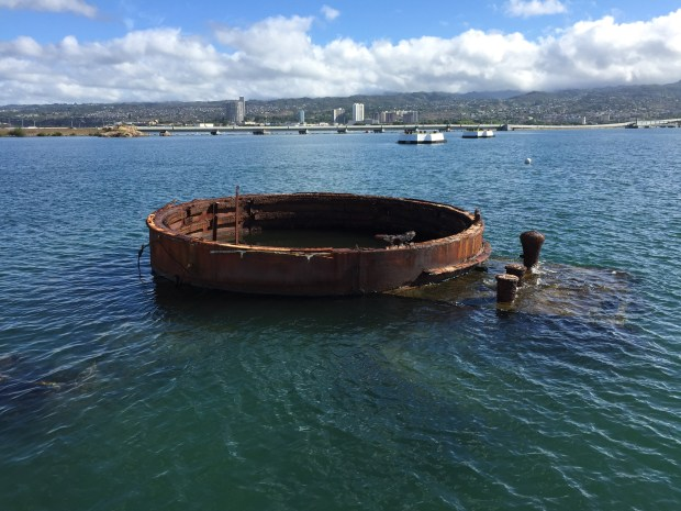 The rusting hull of the USS Arizona can be viewed from the memorial.  A small amount of oil continues to leak from the underwater tanks of the ship.
