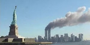The World Trade Center emits smoke off in the distance from the Statue of Liberty on 9/11.