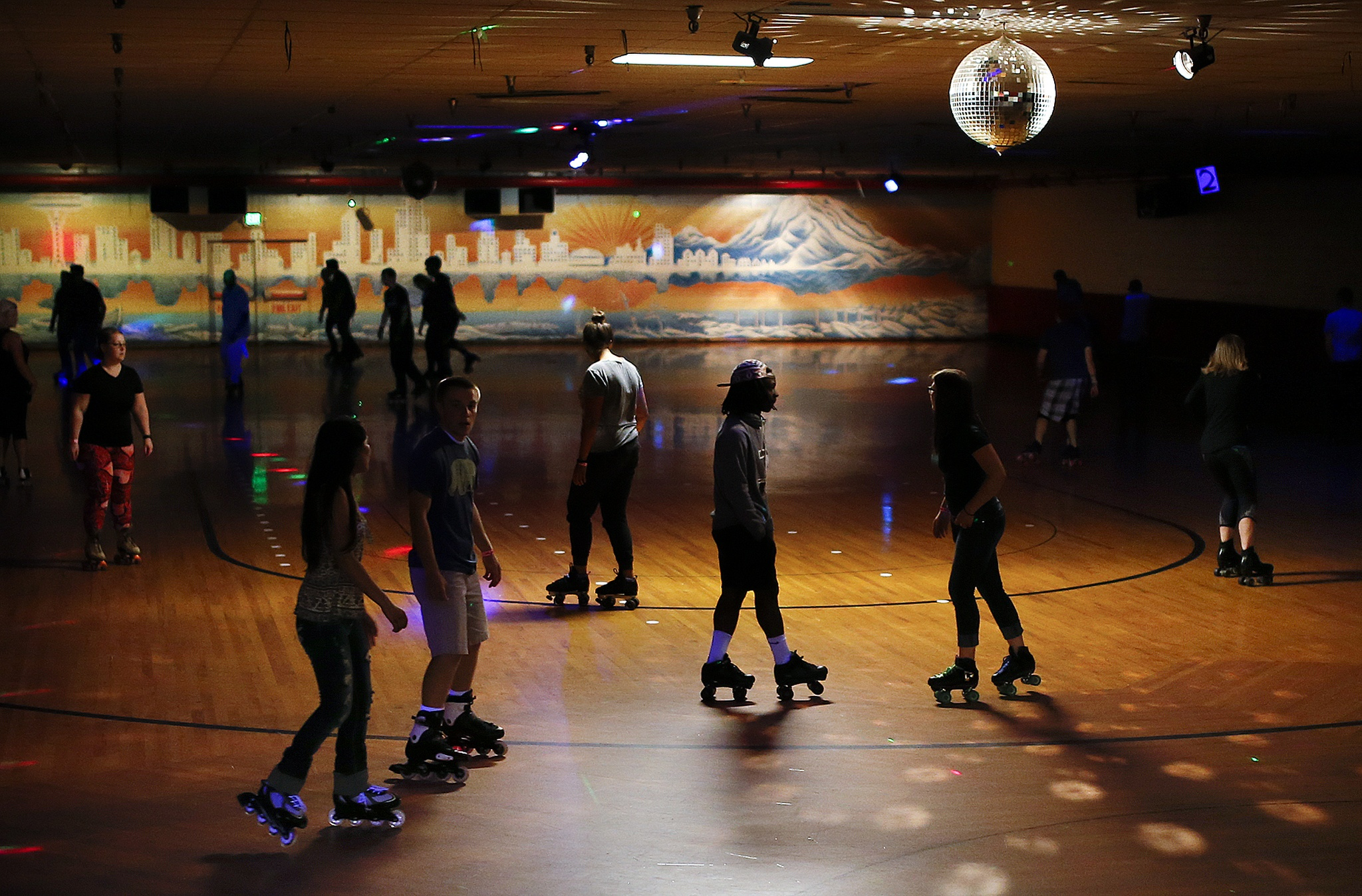 Skaters roll across the floor during a public session at lynnwood bowl and skate on thursday