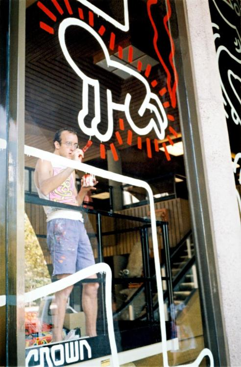 "twixnmix:Keith Haring painting the National Gallery of Victoria mural in Australia, February 1984.  In 1984 during a three week visit to Australia, New York artist Keith Haring undertook a number of public art events. The artist's willingness to create a deliberately ephemeral work at the NGV, on glass, accorded with ""Haring's desire to devaluate a presumed superiority of individualistic drawing on paper or canvas over other kinds of cultural artefacts, considering all surface as having equal worth.""Haring first set up the small ghetto-blaster he carried everywhere, which was decorated by artist Kenny Scharf. John Buckley recalled him at work:""With his beaut little Kenny Scharf radio that he brought over with him from New York, that was blasting away the whole time. He loved the scissor-lift. He was like a kid with a new toy, because he had never been on a scissor-lift before, andhe just had the best fun with that. [Before too long] he was a pro with it; he knew how to manoeuvre it in the finest possible way.""Haring had been brought to look at the window only a day or two before he began the mural. Without any template or grid-lines he painted porportionally without any hestiation or mistakes. Haring painting constantly at eye level, not needing to move the cherry picker back to judge how the whole might be coming together. As Haring himself observed at this time:""One of the things I have been most interested in is the role of chance in situations – letting things happen by themselves. My drawings are never pre-planned. I never sketch a plan for a drawing, even for huge wall murals.""  Haring was also happy to be interrupted at any point, frequently stopping his painting to talk to visiting schoolchildren, sign autographs and quickly sketch souvenir drawings for curious new fans of his work – returning to the mural after each of these intermissions without missing a beat.https://www.ngv.vic.gov.au/essay/fragile-memories-keith-haring-and-the-water-window-mural-at-the-national-gallery-of-victoria/"