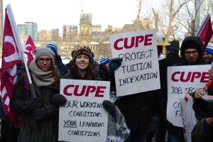 CUPE 3903 members holding picket signs and flags.