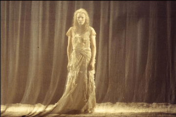 Young white woman in floaty dress behind gauze curtain.