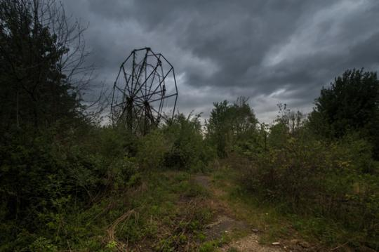 The photo pictured here is of an abandoned theme park in Ohio. It's haunting–it looks more like the scene of a horror flick.. But it's real. It is also among many other strange abandoned structures across the world. Seph Lawless, an amazing photographer who has done the same thing with abandoned malls, is focusing attention on closed amusement parks.. His newest work is labeled BIZARRO.You can see examples of his work here..But I really recommend you purchase his book–you can also peruse his site to look at some of the amazing empty malls he has photographed. (I personally think my local mall may be next.)I have been following Lawless for some time. He is an amazing artist who makes a point with his work. Often, he puts himself in dangerous situations to get the perfect shot.. He did that with his work on malls, and clearly now the same thing with abandoned amusement parks…Each photo represents a story–with that has laughter in the past with the smell of cotton candy in the air and the sound of organ music. Today lifelessness.. Sadness.. emptiness. Each photograph has a story, if not a multitude of tales under the stars of a warm summer night…..