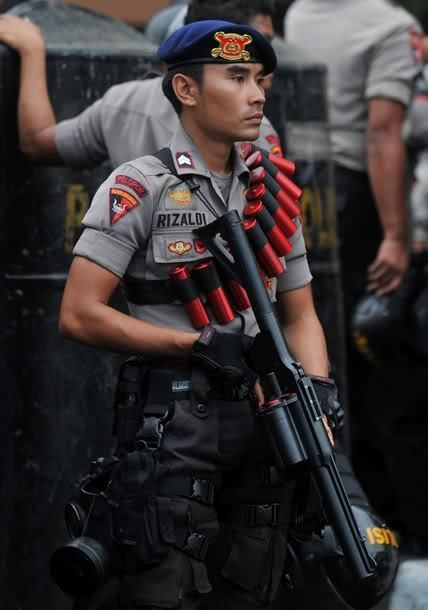 An Indonesian police officer standing ready with a tear-gas - military police officer sample resume