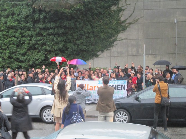 Large crowd fills the sidewalk in the rain