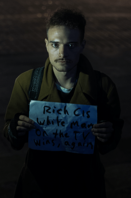 Video artist Manuel D. Lira shows the sign he made for the occasion, which reads 'Rich Cis White Man on the TV Wins, Again.' Photo by Sandra Blow