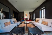 The living room, with black-painted wall paneling,...