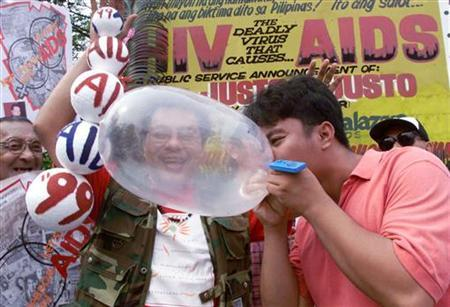 A Filipino AIDS awareness advocate blows up a condom during a street campaign to encourage safe sex on World AIDS Day in Manila