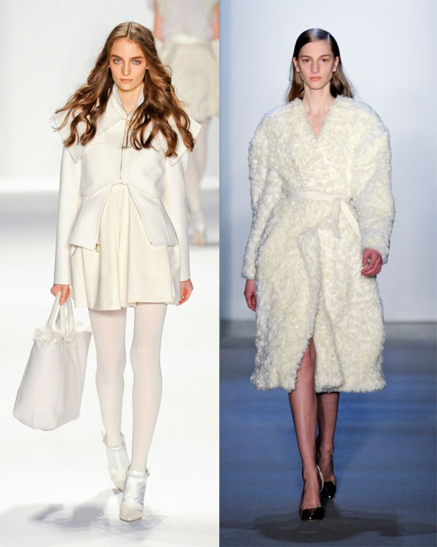 Two models walking the runway in white winter coats.