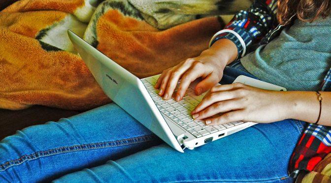 teenage-girl-typing-on-white-laptop-edited