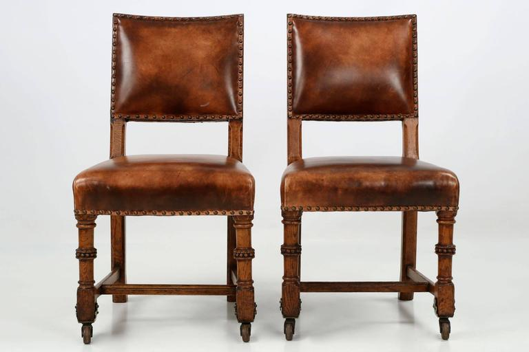 Pair of english antique leather and carved oak side chairs