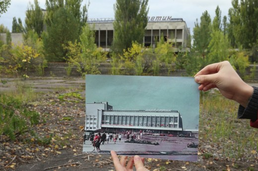 """PRIPYAT, UKRAINE - SEPTEMBER 29:  An assistant holds up a photo showing the city of Pripyat's main square and the """"Energetik"""" cultural center before 1986 at the same site that today is abandoned and overgrown with trees on September 29, 2015 in Pripyat, Ukraine. Pripyat lies only a few kilometers from the former Chernobyl nuclear power plant and was built in the 1970s to house the plant's workers and their families. On April 26, 1986, technicians at Chernobyl conducting a test inadvertently caused reactor number four to explode, sending plumes of highly radioactive particles and debris into the atmosphere. Authorities evacuated 120,000 people from the area, including 43,000 from Pripyat. Today Pripyat is a ghost-town, its apartment buildings, shops, restaurants, hospital, schools, cultural center and sports facilities derelict and its streets overgrown with trees. The city lies in the inner exclusion zone around Chernobyl where hot spots of persistently high levels of radiation make the area uninhabitable for thousands of years to come.  (Photo by Sean Gallup/Getty Images)"""