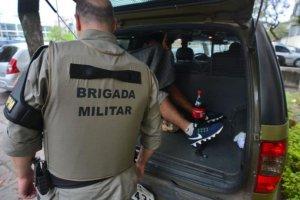 Um preso segue em viatura da Brigada Militar na frente da 2ª DPPA | Foto: Guilherme Testa