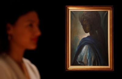 "A worker at Bonhams auctioneers poses next to Tutu,"" by Nigeria's best-known modern artist Ben Enwonwu, ahead of its sale, in London, Britain February 7, 2018. REUTERS/Peter Nicholls"