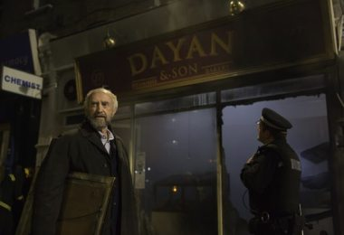 Nat (Jonathan Pryce) stands in front of his burned out bakery