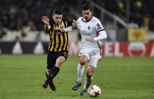 AC Milan's Andre Silva (R) fights for the ball with AEK's Kostas Galanopoulos (L) during  the UEFA Europa League Group D football match between AEK Athens and AC Milan at the OAKA stadium in Athens on November 2, 2017. / AFP PHOTO / Louisa GOULIAMAKI