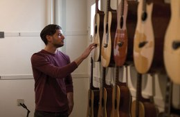 Eric Jay strums through memories at Mandolin Brothers, which is up for sale. Kirsten Luce photo for The New York Times