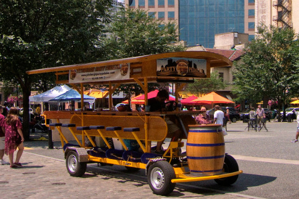 people ride through the streets of pittsburgh on a mobile bicycle bar