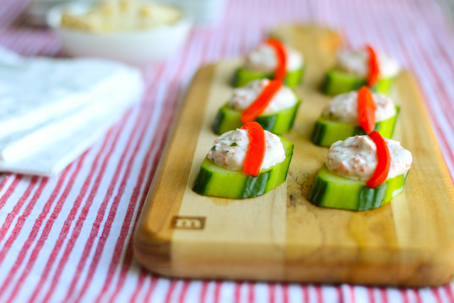 Cucumber rounds topped with a savory greek yogurt vegetable dip, perfect for parties!