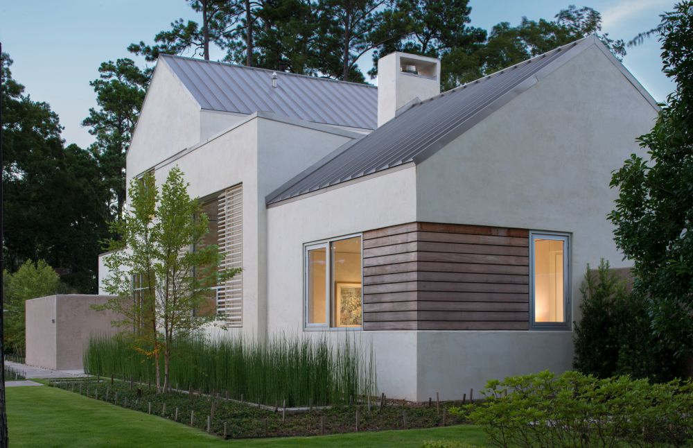 Linear garapa wood window accents coordinate with the custom metal shutters beyond, standing seam metal roof above, and the horsetail reed landscaping across the front.