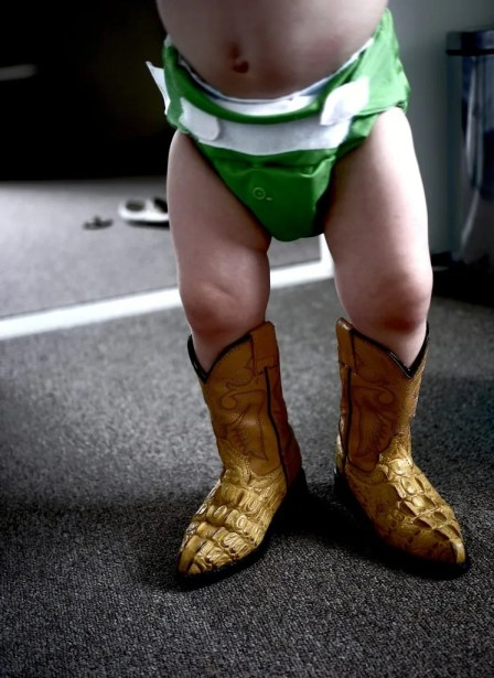 baby in cowboy boots and cloth diaper
