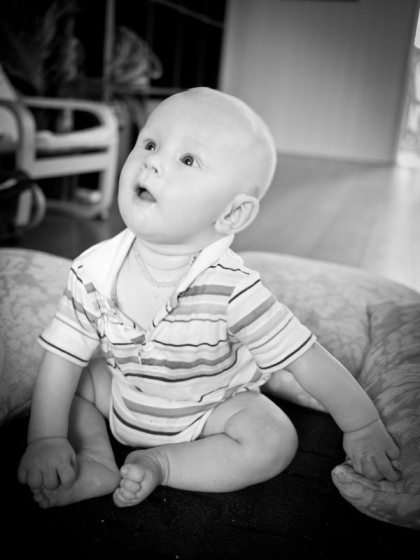 baby sitting up in black and white