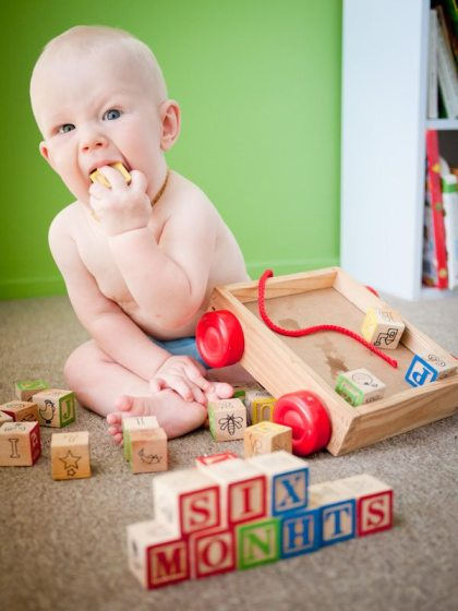 six month on baby chomping on a block