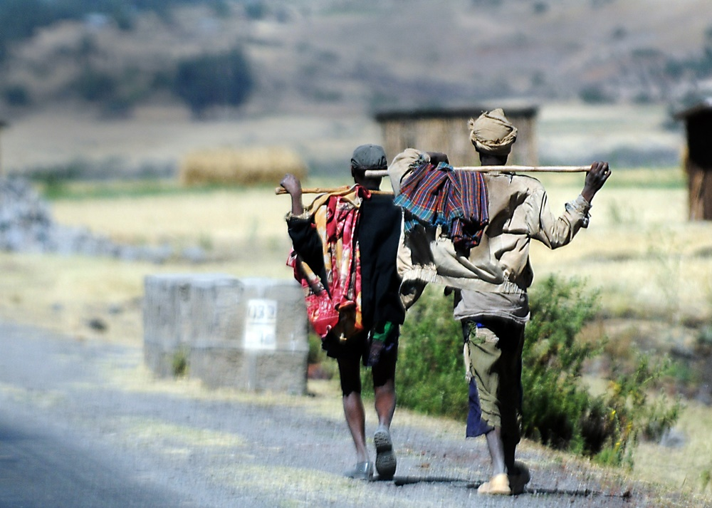 Two men walk along the road to Addis Ababa, Ethiopia, Dec. 8. People in Ethiopia may choose to leave their rural homes and walk to the cities to seek work.