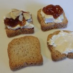 Four Steps: Mini-toast, spread mini-toast with Laughing Cow cheese, add fig jam, top with toasted sliced almonds (Photo Credit: Adroit Ideals)