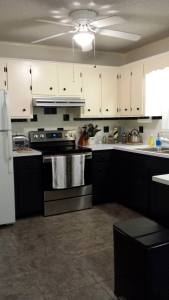 """The kitchen """"AFTER"""" photo.  I love the black paint on the bottom cabinets! (Photo Credit: Adroit Ideals)"""