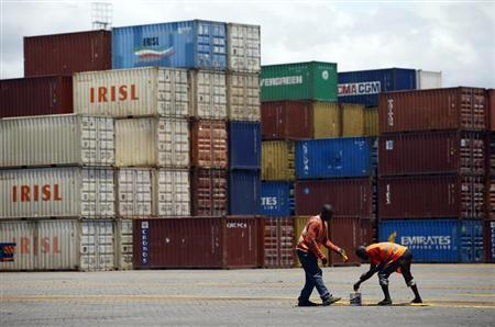 Workers paint the ground in front of containers at the main port in the Kenyan coastal city of Mombasa