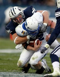 """Bringham Young defensive end Jan Jorgensen, pictured tackling Air Force quarterback Ben Cochran, said at a press conference before playing Air Force that the Falcons play """"legal, but dirty."""" (AP photo)"""