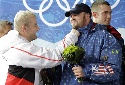 Germany's Andre Lange, left, gives the United States' Steven Holcomb a playful punch during the flower ceremony after the men's four-man bobsled final competition Saturday. Lange's team won the silver and Holcomb's team won the gold. (AP Photo/Michael Sohn)