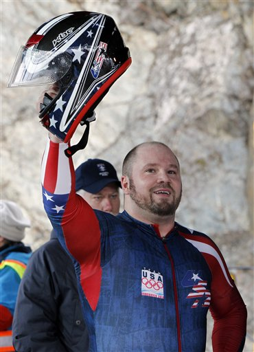 USA-1 driver Steven Holcomb waves to the crowd after the third run during the men's four-man bobsled final competition  Saturday. (AP Photo/Michael Sohn)