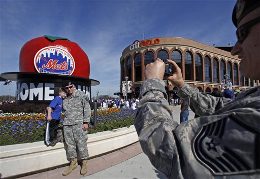 Gary Brown takes a photograph of New York Army National Guardsman Erich Schmidt and his 5-year-old son Alex in front of the Home Run apple before the New York Mets home opener at Citi Field on Monday. (AP Photo/Kathy Willens)