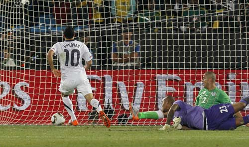 Landon Donovan scores the game-winner past Algeria goalkeeper Rais M'Bolhi. (AP Photo/Eugene Hoshiko)