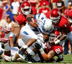 Air Force quarterback Tim Jefferson, center, is brought down by three Oklahoma defenders. (Sue Ogrocki / The Associated Press)