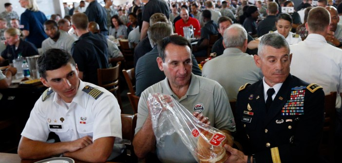 U.S. men's national basketball team head coach Mike Krzyzewski, center, breaks bread with Lt. Gen. Robert Caslen, superintendent of the U.S. Military Academy, during a visit to the school with Team USA in August 2014. (Associated Press photo by Mike Groll)