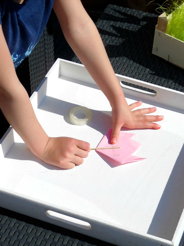 Child taping skewer to the back of a paper tulip flower