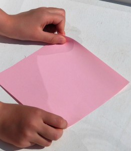 child's hands holding craft paper