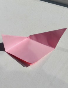 Photo instructions showing how to fold a square of paper to make a simple tulip