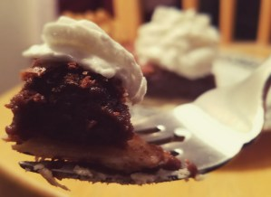 a bite of chocolate pie topped with whipped cream on a fork