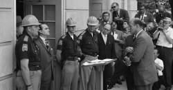Attempting to block integration at the University of Alabama, Governor George Wallace stands defiantly at the door while being confronted by Deputy U.S. Attorney General Nicholas Katzenbach.