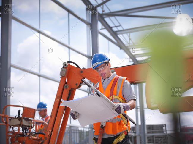 Construction worker reading blueprints stock photo - OFFSET