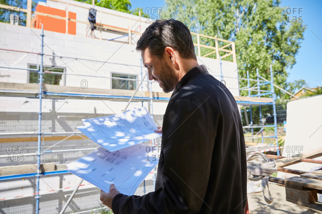 Businessman reading blueprints while standing at construction site - reading blueprints