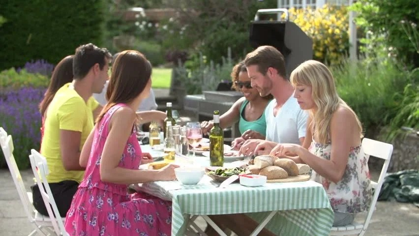 Group Of Friends Sitting Around Table Enjoying Outdoor