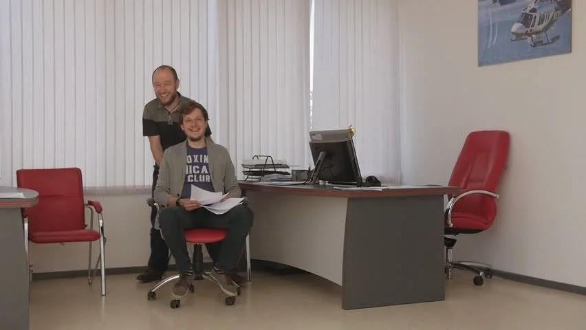 Stock Video Clip of Office chair race Slow motion Young guys - office fun games