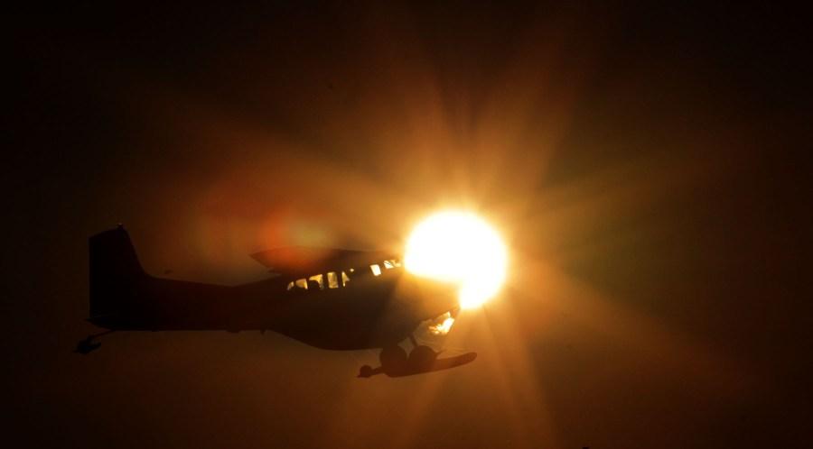 Cessna on skis against the sun
