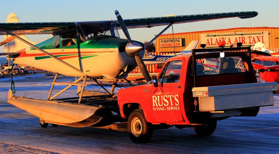 Cessna 170 on floats being moved by specially modified truck to move aircraft on floats away from Lake Hood for the winter.