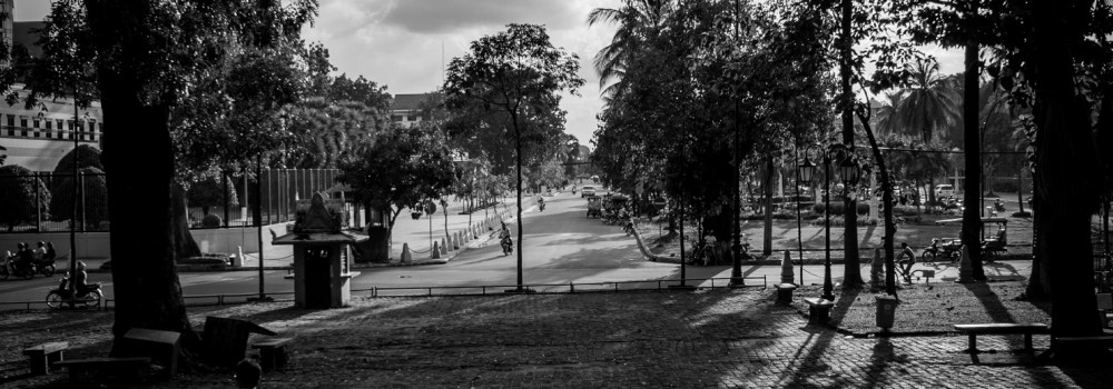 Looking north, Khmer children and adults walk among the the long shadows cast by the trees that skirt Wat Phnom temple in Phnom Penh.